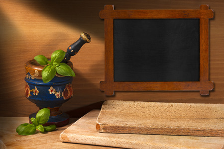 Rustic and empty blackboard, old wooden mortar and pestle with basil leaves on wooden wall with chopping board photo