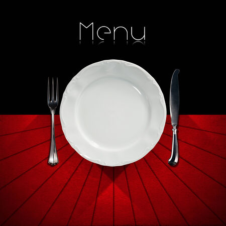 Restaurant menu with empty plate and cutlery, fork and knife, on a black and red background with shadows and written menu photo