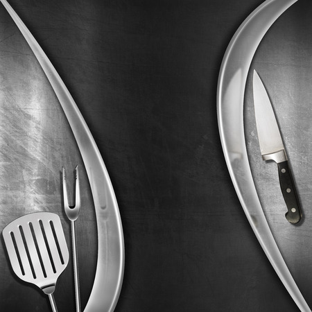 Modern blackboard with metal frame, kitchen utensils and knife on brushed steel background. Template for recipes or a food menu photo