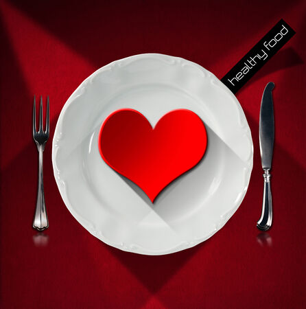 Red heart on the white plate with silver cutlery, fork and knife, on red velvet background with shadows. Concept of healthy food photo