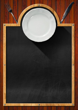 Blackboard with wooden frame, empty white plate and silver cutlery, fork and knife, on a wooden wall. Template for recipes or food menu photo