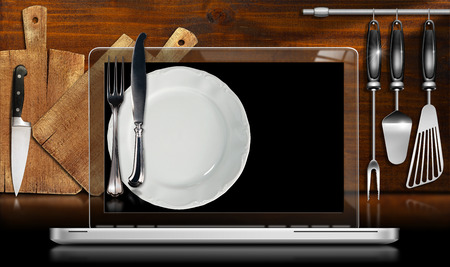 Laptop computer with black screen and empty plate and cutlery, in a kitchen with cutting boards and utensils on wooden wall photo