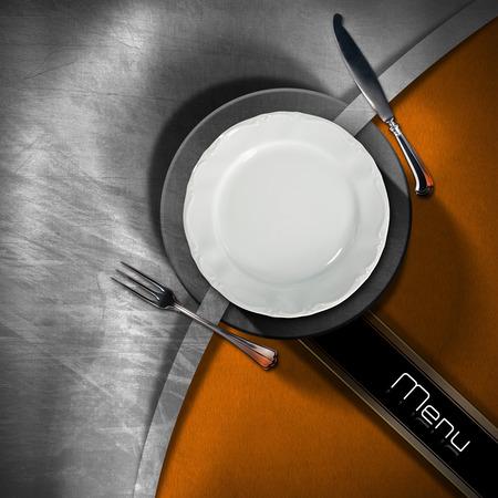 black metallic background: Restaurant menu with empty plate and cutlery, on metallic and orange velvet background with diagonal black band with written menu