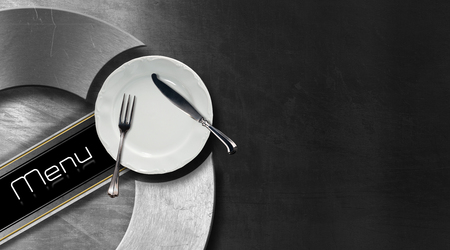 Horizontal restaurant menu with empty white plate and cutlery, fork and knife, on black and metal background with metallic circle and diagonal black band photo