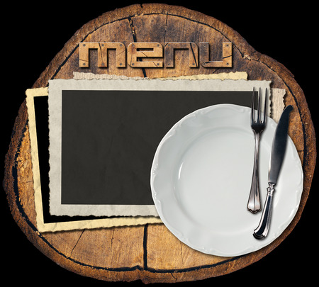 Section of tree trunk with empty photo frames, empty white plate with silver cutlery, written menu with wooden font. Background for a rustic menu photo