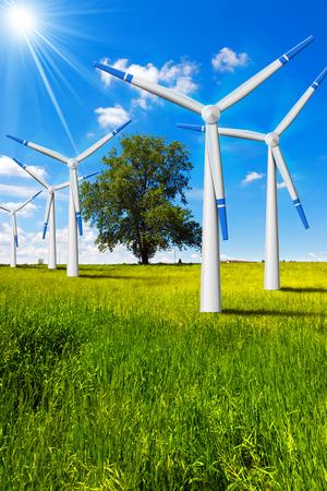 energia electrica: Cinco turbinas de viento en el campo con �rboles, cielo azul, las nubes y los rayos del sol