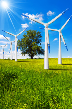 energy supply: Five wind turbines in countryside with tree, blue sky, clouds and sun rays Stock Photo