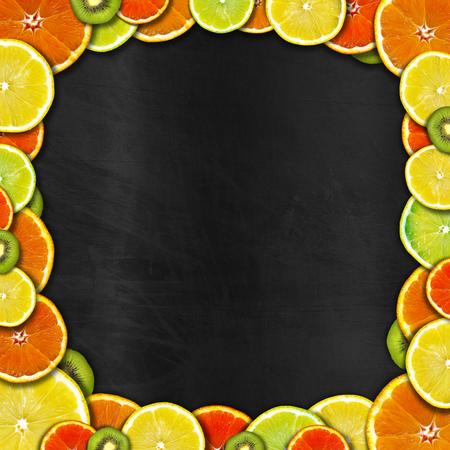 Frame of oranges, lemons and kiwi on an empty blackboard photo