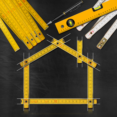 housing project: House project concept. Wooden meter ruler in the shape of house with drawing, propelling pencil, two meter tools and spirit level on a blackboard