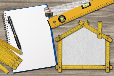 House project concept. Wooden meter ruler in the shape of house with pencil, empty notebook, two meter tools and spirit level on a wooden desk photo