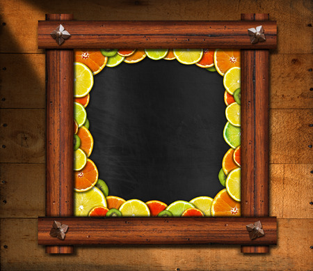 Blackboard with wooden frame and ancient nails with oranges, lemons and kiwi on wooden background photo