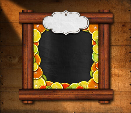Blackboard with wooden frame and an empty label with oranges, lemons and kiwi on wooden background photo