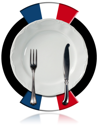 Concept of French cuisine with empty white plate and silver cutlery on black circle with two French flags isolated on white background photo