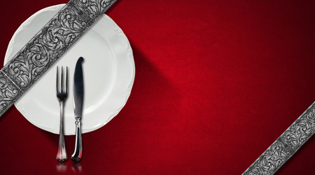 Red velvet background with diagonal silver floral bands, empty white plate and silver cutlery. Template for an elegant restaurant menu photo