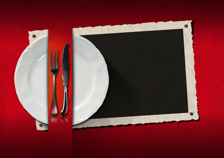Empty photo frame with empty white plate and silver cutlery on red velvet background. Template for an elegant restaurant menu