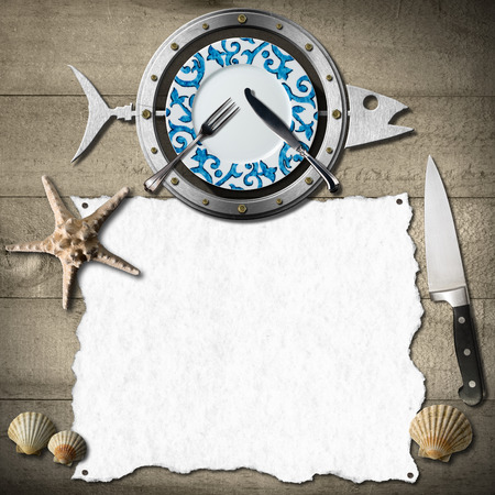 Restaurant seafood menu with metal fish, plate, fork and knife, seashells and starfish, kitchen knife, empty white paper on a wooden background photo