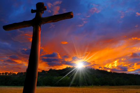 churches: Cross silhouette at the beautiful sunset over the hill with cloudy sky Stock Photo