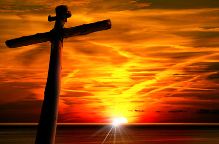 cruz roja: Silueta cruzada en la hermosa puesta de sol sobre el mar con el cielo nublado. Foto de archivo