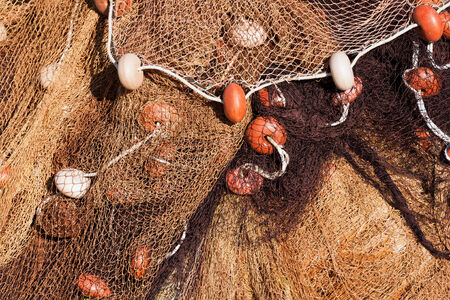 Close up of fishing net with ropes and floats in the harbor photo
