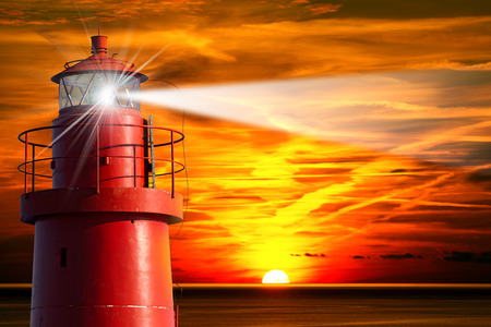 The top of a red and metallic lighthouse with light beam at sunset with clouds