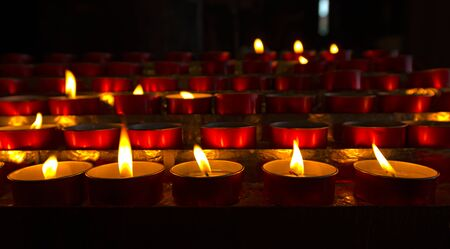votive: A group of red votive candles light the darkness in church