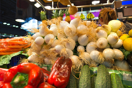 White onions, red peppers, carrots, cucumbers and lemons in La Boqueria, the most famous market in Barcelona photo
