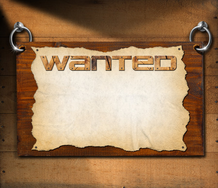 Dark wooden sign board with torn empty parchment with written wanted. Hanging on a wooden wall. photo