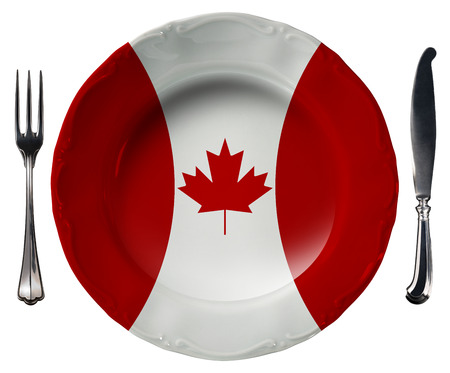 Concept of Canadian cuisine with empty plate colored with the colors of Canadian flag and silver cutlery isolated on white background photo