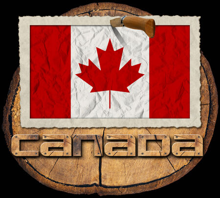 Flag of Canada in a old photo frame with wooden text canada on a section of tree trunk isolated on black background photo