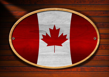 Oval wooden canadian flag with screws on a wooden wall with planks photo