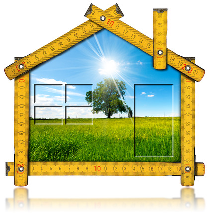 Wooden yellow meter ruler in the shape of house with country landscape with tree inside. Isolated on white background photo