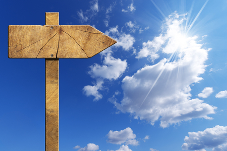 directional sign: Wooden directional sign with one empty arrow on a blue sky with clouds and sun rays