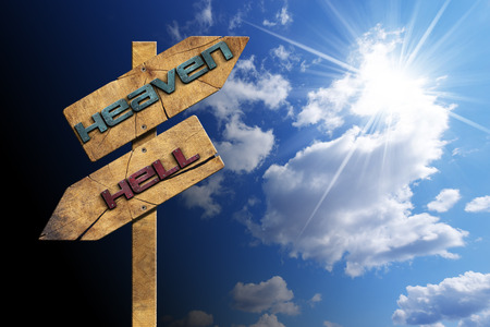 Wooden directional sign with two arrows in opposite direction with text heaven and hell on blue sky with clouds and sun rays Stockfoto
