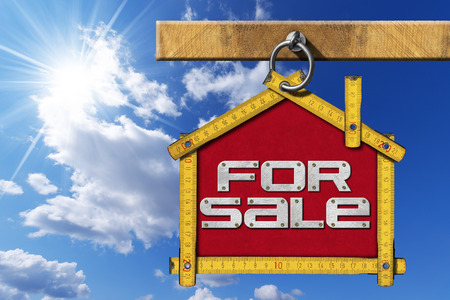 house for sale: Yellow wooden meter ruler in the shape of house with text for sale. For sale real estate sign on blue sky with cloud and sun rays Stock Photo