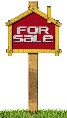 Yellow wooden meter ruler in the shape of house with text for sale. For sale real estate sign isolated on white background with grass photo