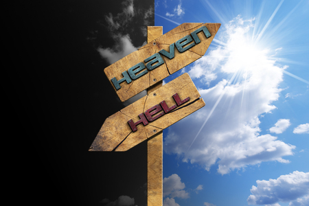 Wooden directional sign with two arrows in opposite direction with text heaven and hell on blue and black sky with clouds and sun rays