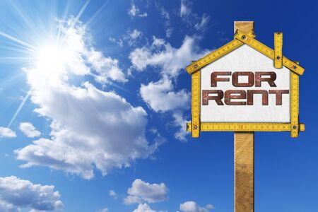 house for rent: Yellow wooden meter ruler in the shape of house with text for rent. For rent real estate sign on blue sky with clouds and sun rays