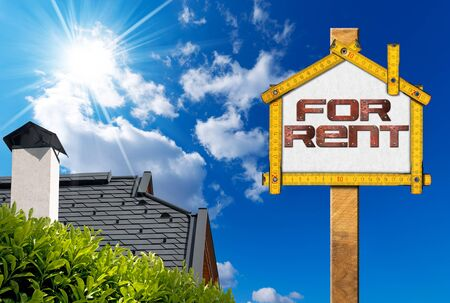 house for rent: Yellow wooden meter ruler in the shape of house with text for rent. For rent real estate sign on blue sky with roof, clouds and sun rays