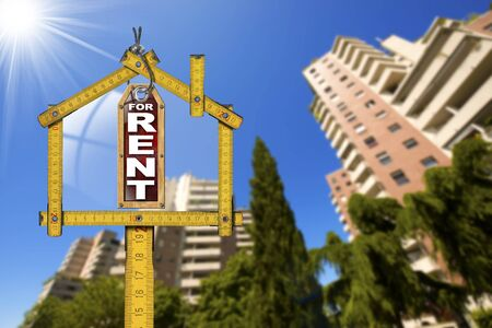 for rent: Yellow wooden meter ruler in the shape of house and label with text for rent. For rent real estate sign with tall and blurred buildings in the background