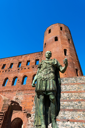 palatine: Roman statue of Julius Caesar and ancient ruins of Palatine Towers in Torino, Piemonte, Italy Stock Photo