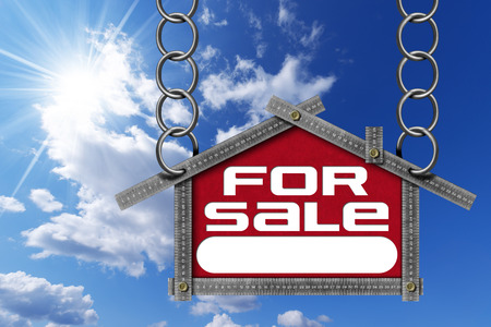 metallic  sun: Grey metallic meter ruler in the shape of house with text for sale. For sale real estate sign on blue sky with clouds and sun rays