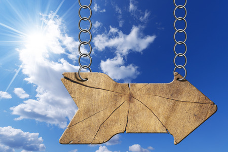 directional sign: Wooden directional sign with one empty arrow hanging with metal chain on blue sky with clouds and sun rays Stock Photo