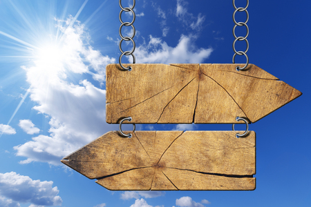 directional sign: Wooden directional sign with two empty arrows in opposite direction hanging with metal chain on blue sky with clouds and sun rays Stock Photo