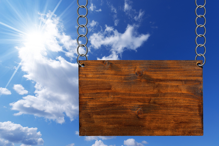 ring road: Empty wooden sign hanging with metallic chain on blue sky with clouds and sun rays