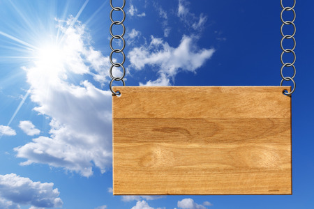 metallic  sun: Empty wooden sign hanging with metallic chain on blue sky with clouds and sun rays