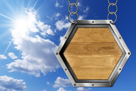 metallic  sun: Empty hexagonal wooden sign with metallic frame hanging with metal chain on blue sky with clouds and sun rays