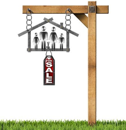 Meter ruler in the shape of house with symbol of a family label with text for sale. Hanging from a chain on a wooden pole. Isolated on white with green grass photo