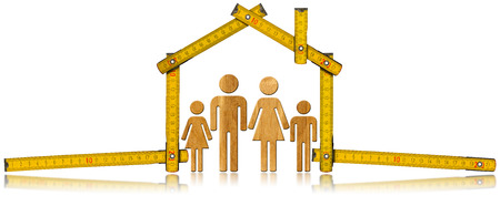 Yellow wooden meter ruler in the shape of house isolated on white background with symbol of a family. House project concept. photo
