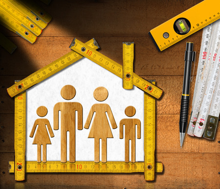 two level house: House project concept. Meter ruler in the shape of house with symbol of a family pencil two meter tools and spirit level on wooden background