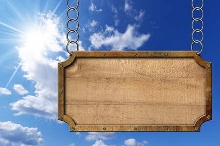 metallic  sun: Empty rectangular wooden sign with metallic brown frame hanging with metal chain on blue sky with clouds and sun rays Stock Photo